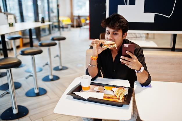 Stilvoller und lustiger indischer mann, der am schnellimbisscafé sitzt und hamburger isst und telefonisch selfie macht. Premium Fotos