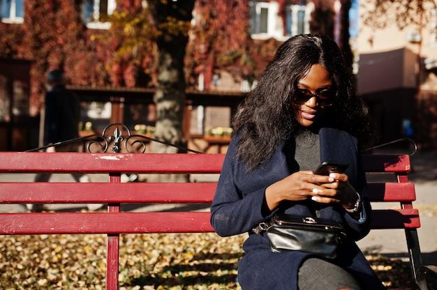 Stilvolles afroamerikanermädchen im blauen mantel und in der sonnenbrille stellte am sonnigen herbsttag auf bank und unter verwendung ihres handys auf. afrika-modellfrau mit smartphone. Premium Fotos