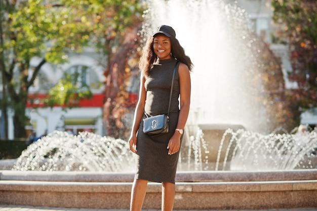 Stilvolles afroamerikanermädchen in der grauen tunika, in der umhängetasche und in der kappe stellte sich am sonnigen herbsttag gegen brunnen auf. afrika modellfrau. Premium Fotos