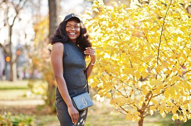 Stilvolles afroamerikanermädchen in grauer tunika, umhängetasche und kappe, die am sonnigen herbsttag gegen gelbe blätter gestellt werden. afrika modellfrau. Premium Fotos