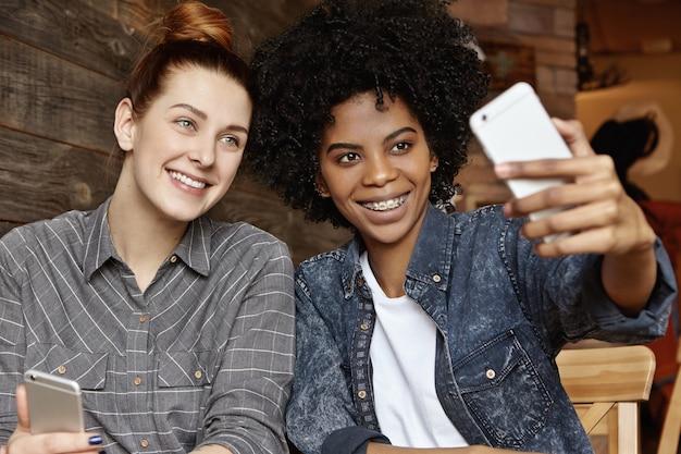 Stilvolles afroamerikanisches mädchen mit afro-haarschnitt, der handy hält und selfie nimmt Kostenlose Fotos