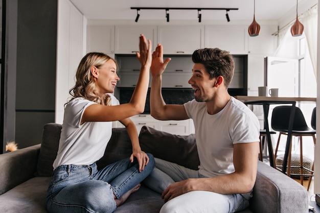 Stilvolles blondes mädchen, das mit freund im wohnzimmer spielt. innenporträt von scherzenden jungen leuten. Kostenlose Fotos
