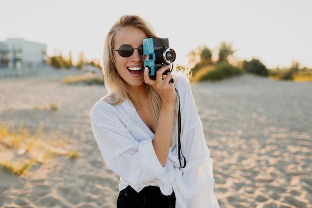 Stilvolles formschönes mädchen mit retro-kamera, die auf sonnigem strand aufwirft. sommerurlaub. tropische stimmung. freiheits- und reisekonzept. Kostenlose Fotos