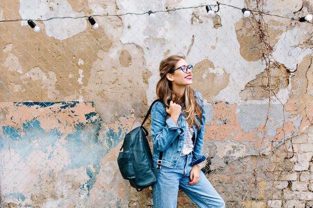 Stilvolles hipster-mädchen im retro-jeansanzug, der vor der alten mauer aufwirft. trendy junge frau mit tasche, die neben altem gebäude steht. Kostenlose Fotos