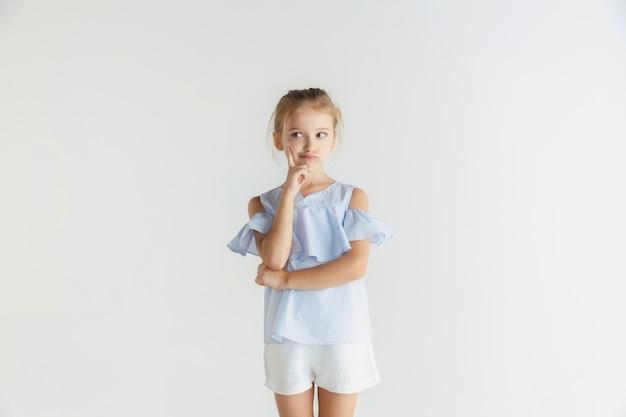 Stilvolles kleines lächelndes mädchen, das in der freizeitkleidung lokalisiert auf weißem studio aufwirft Kostenlose Fotos