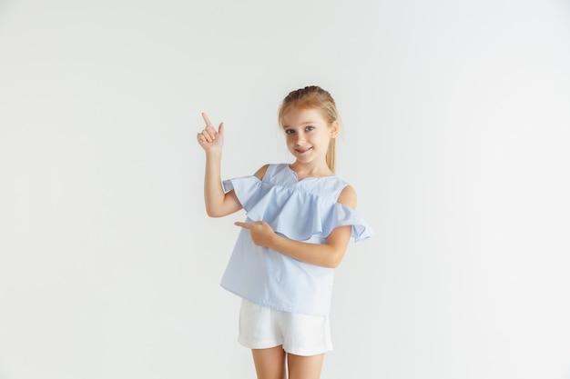 Stilvolles kleines lächelndes mädchen, das in der freizeitkleidung lokalisiert auf weißer wand aufwirft. kaukasisches blondes weibliches modell. menschliche gefühle, gesichtsausdruck, kindheit. zeigen auf eine leere leertaste. Kostenlose Fotos