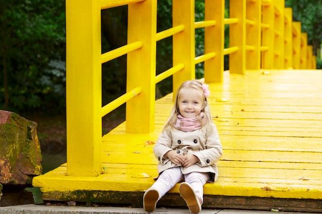 Stilvolles kleines mädchen auf einer gelben brücke im park Premium Fotos