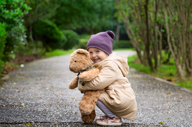 Stilvolles kleines mädchen, das ihren angefüllten teddybären im herbstpark umfasst Premium Fotos