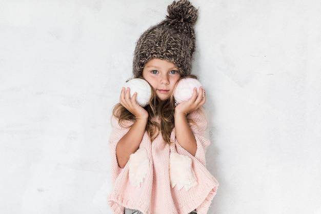 Stilvolles kleines mädchen, das schneebälle hält Kostenlose Fotos