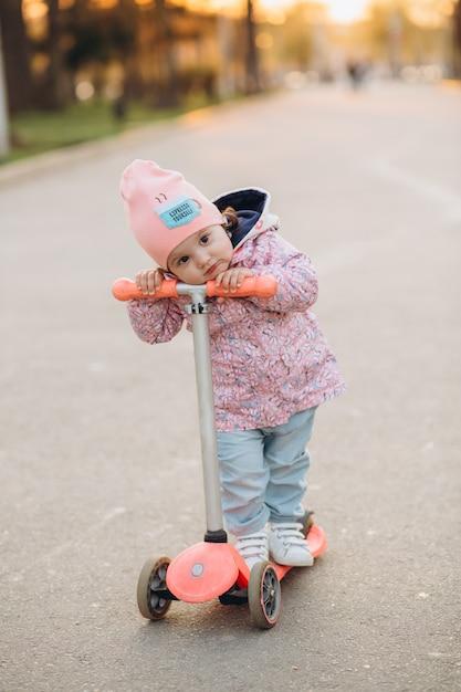Stilvolles kleines mädchen reitet einen roller im park bei sonnenuntergang Premium Fotos