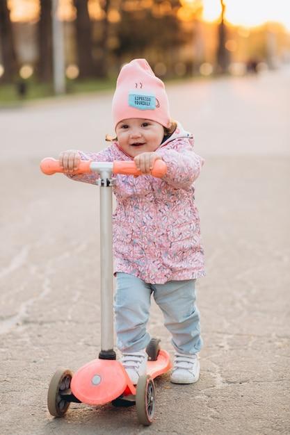 Stilvolles lächeln des kleinen mädchens und reitet einen roller im park bei sonnenuntergang Premium Fotos