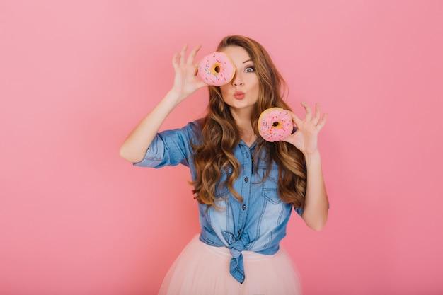 Stilvolles mädchen mit langen lockigen haaren posiert positiv und hält frische rosa donuts mit puder bereit, um süßigkeiten zu genießen. porträt der attraktiven jungen frau im retro-jeanshemd, das spaß mit süßem zeug hat Kostenlose Fotos