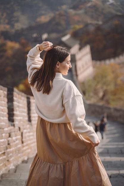 Stilvolles mädchen, welches die chinesische mauer nahe peking während der herbstsaison besucht. Kostenlose Fotos