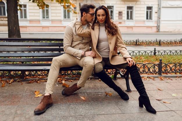 Stilvolles paar in der liebe, die im freien aufwirft. herbstmodetrends. brünettes modell mit stilvollem kerl im beigen mantel, der auf bank sitzt. Kostenlose Fotos