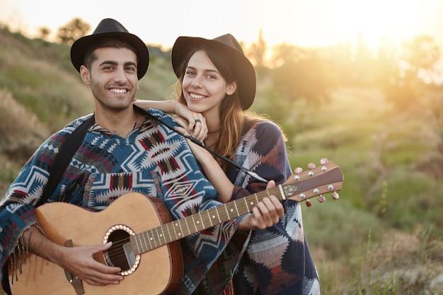 Stilvolles paar mit gitarre auf dem feld Kostenlose Fotos