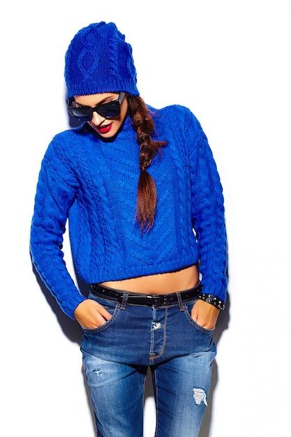 Stilvolles schönes modell der jungen frau des zaubers mit den roten lippen im blauen strickjackenhippie-stoff im beanie Kostenlose Fotos