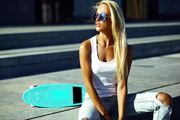 Stilvolles sexy schönes junges blondes vorbildliches mädchen des blickes der hohen mode zauber im hellen zufälligen hippie des sommers kleidet mit dem skateboard, das in der straße sitzt Kostenlose Fotos