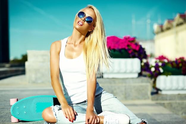 Stilvolles sexy schönes junges blondes vorbildliches mädchen des blickes der hohen mode zauber im hellen zufälligen hippie des sommers kleidet mit skateboard hinter blauem himmel in der straße Kostenlose Fotos