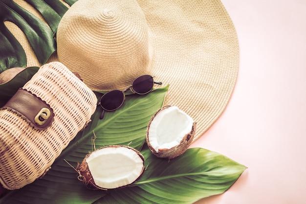 Stilvolles sommerstillleben mit strandhut und kokosnuss auf einem rosa hintergrund, pop-art. draufsicht, nahaufnahme, kreatives konzept Kostenlose Fotos