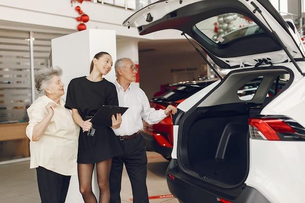 Stilvolles und elegantes altes ehepaar in einem autosalon Kostenlose Fotos