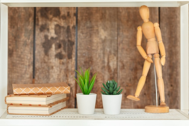 Stilvolles weißes bücherregal gegen hölzerne wand des schmutzes Premium Fotos