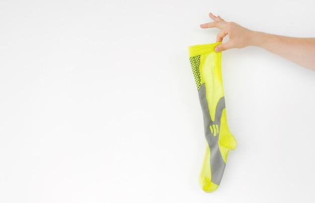 Stinkende gelbe laufsportsocke in der hand isoliert Premium Fotos