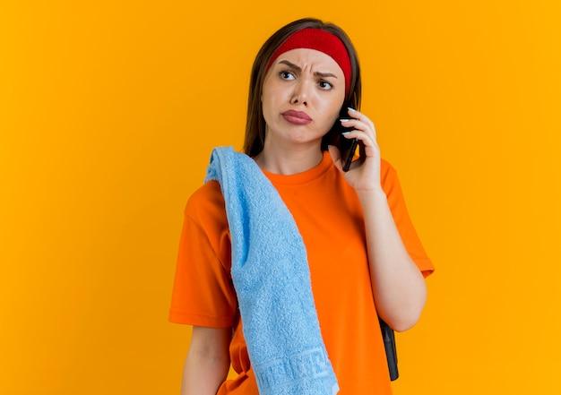 Stirnrunzelnde junge sportliche frau, die stirnband und armbänder mit springseil und handtuch auf schultern trägt und am telefon spricht, das seite betrachtet Kostenlose Fotos