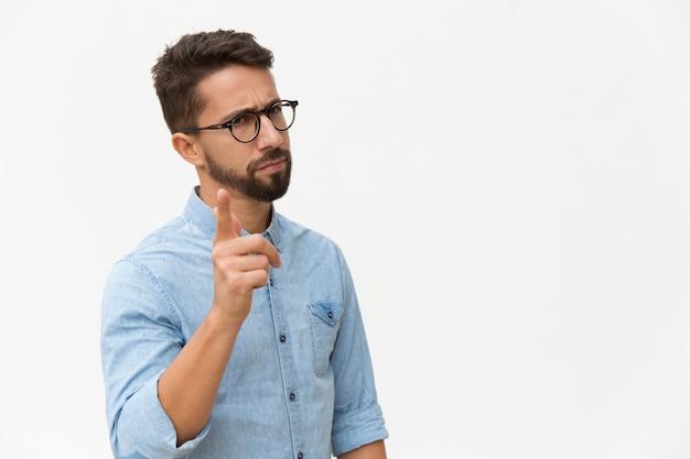 Stirnrunzelnder betroffener kerl, der finger rüttelt Kostenlose Fotos