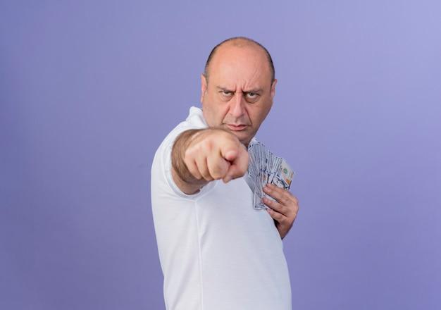 Stirnrunzelnder lässiger reifer geschäftsmann, der in der profilansicht steht, geld hält und auf kamera lokalisiert auf lila hintergrund mit kopienraum zeigt Kostenlose Fotos