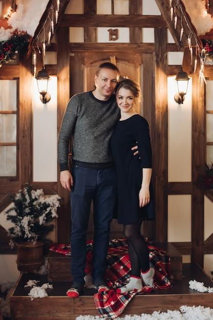 Stock foto porträt des schönen jungen erwachsenen paares sitzen kuscheln auf holzbank in weihnachten interieur Premium Fotos