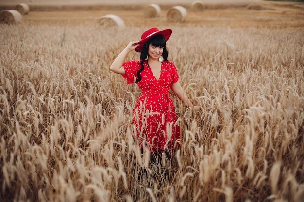 Stock foto porträt einer wunderschönen erwachsenen frau mit langen dunklen haaren tragen leuchtend rot tupfen kleid und roten hut lächelnd Premium Fotos