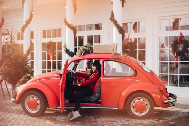 Stockfoto einer hübschen frau im roten pullover, der im modischen roten auto sitzt. weihnachtsdekorationen. Kostenlose Fotos