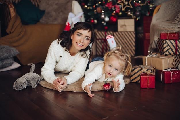 Stockfoto porträt der attraktiven jungen erwachsenen mutter mit der kleinen blonden tochter, die auf dem holzboden über kissen mit eingewickelten weihnachtsgeschenken liegt. mädchen spielt mit rotem weihnachtsball. Kostenlose Fotos