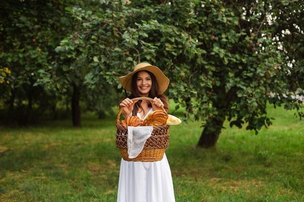 Stockfoto porträt einer schönen brünetten frau im sommerhut und im weißen kleid, die frische hausgemachte bäckerei im braunen geflochtenen korb in ihren händen demonstrieren, die im grünen park am sommertag stehen. Premium Fotos