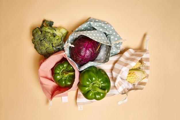Stoff-baumwoll-einkaufstüten für lebensmittel mit gemüse. beiger hintergrund. kein plastik Premium Fotos
