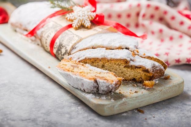 Stollen, ein traditioneller europäischer kuchen mit nüssen und kandierten früchten, wird mit puderzucker bestäubt und in stücke geschnitten Premium Fotos