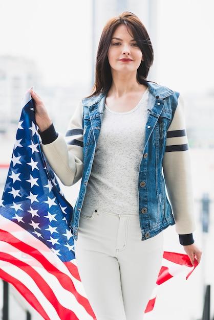 Stolze frau, die mit großer usa-flagge geht Kostenlose Fotos