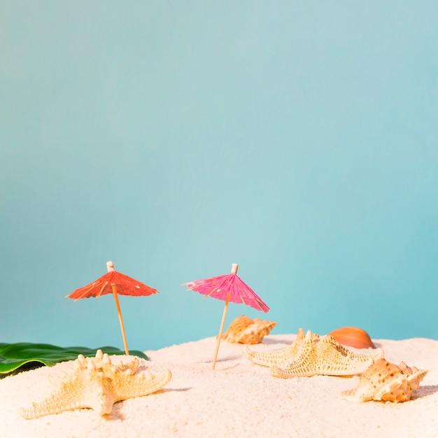 Strand mit roten sonnenschirmen und seesternen Kostenlose Fotos