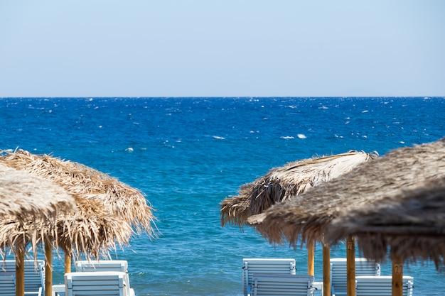 Strand mit sonnenschirmen und liegestühlen am meer in santorini Premium Fotos