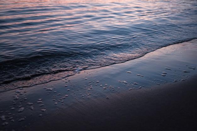 Strand umgeben vom meer unter dem sonnenlicht während des sonnenuntergangs Kostenlose Fotos