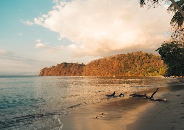 Strand und ruhiger ozean in den sonnenunterganglichtern Kostenlose Fotos