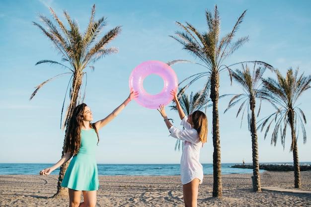 Strand- und sommerkonzept mit den frauen, die mit aufblasbarem ring spielen Kostenlose Fotos