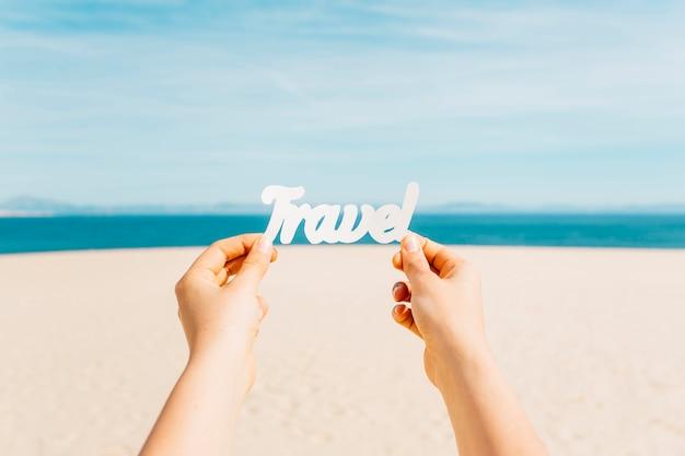 Strandkonzept mit den händen, die reisebuchstaben halten Kostenlose Fotos
