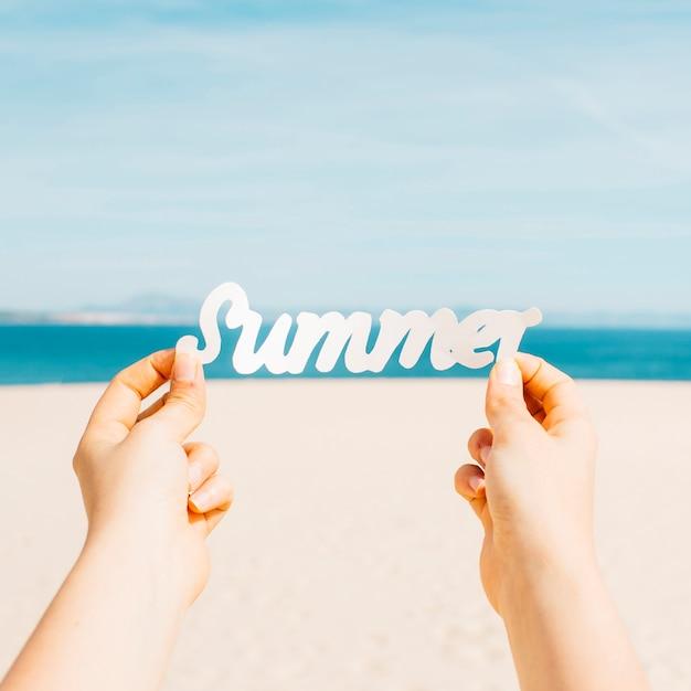 Strandkonzept mit den händen, die sommerbuchstaben halten Kostenlose Fotos