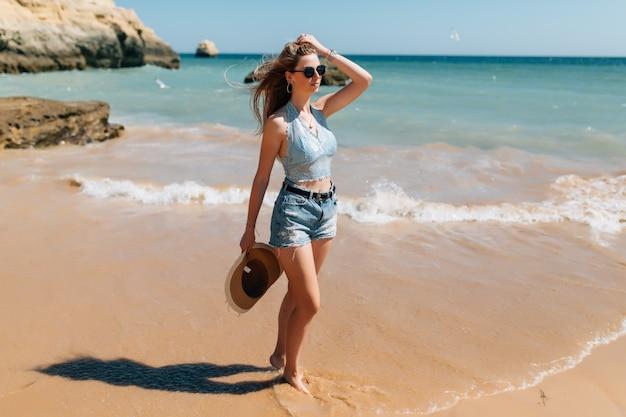 Strandurlaub. schöne frau im sonnenhut, die den perfekten sonnigen tag genießt, der auf dem strand geht. glück und glückseligkeit. Kostenlose Fotos