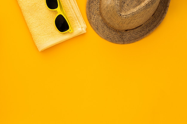 Strandzubehör auf dem gelben hintergrund. sonnenbrillen, handtuch. flip-flops und gestreifter hut. Kostenlose Fotos