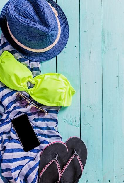 Strandzubehör mit gelbem badeanzug, sonnenbrille und flipflops Premium Fotos