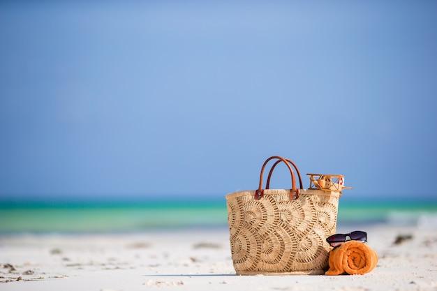 Strandzubehör - spielzeugflugzeug, strohsack, orange handtuch und brillen am strand Premium Fotos