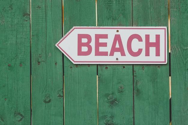 Strandzugangszeichen auf rustikalem grünem bretterzaun. Premium Fotos