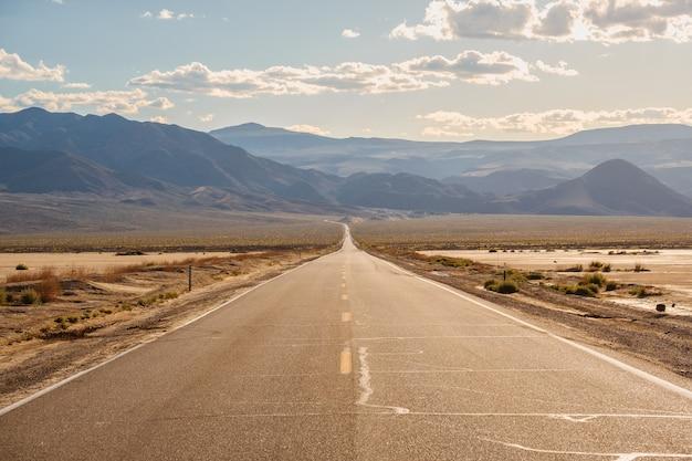 Straße mitten in der wüste mit den herrlichen bergen in kalifornien Kostenlose Fotos